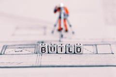 Plan del edificio con el emplear de la palabra gotas y un trabajador modelo fotos de archivo