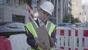 Plan del edificio de la lectura del casco del equipo y del constructor de seguridad del niño pequeño del retrato que lleva, traba almacen de metraje de vídeo