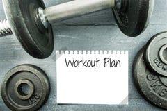 Plan del entrenamiento con pesa de gimnasia en la tabla de madera Fotografía de archivo