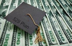 529 plan education money. Graduation cap with 529 Plan text, on hundred dollar bills - college education savings concept Stock Photo
