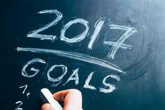 Plan een lijst van doelstellingen voor de hand van 2017 op bord wordt geschreven dat Royalty-vrije Stock Foto's