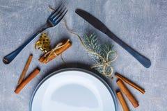 Plan einer weißen Platte und unter ihr eine blaue Platte, zwei Zimtstangen, Zweige der Tanne und Schneeflocken Ansicht von oben Stockbild