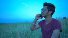 Plan en gros plan, homme indien conduisant une conversation à un téléphone sur le fond du ciel de soirée clips vidéos