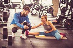 Plan and exercise. Personal trainer with young sports girl sitting on floor and having conversation after exercise. Using digital tablet royalty free stock image