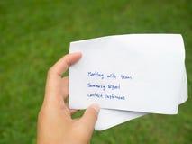 Plan för affär för dag för hållande vitbok för kvinnahand skriftligt Mötelag, summarisk rapport och mötekunder i grön bakgrund Royaltyfria Bilder