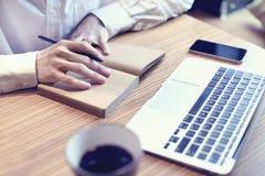 Plan för affär för handstil för redovisningsaffärsman, bruksbärbar datordator och mobiltelefon i kafét som dricker kaffe Fotografering för Bildbyråer