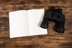 Plan för att resa, kikare på trägolv med anteckningsboken arkivfoton