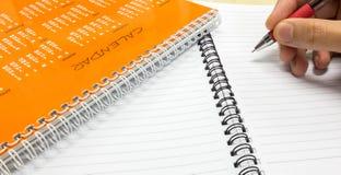 Plan för nytt år, orange kalender med den hållande pennan för man och anteckningsbok på kontorsskrivbordet Arkivbilder