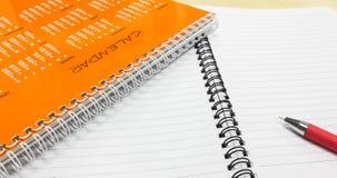 Plan för nytt år, orange kalender med pennan och anteckningsbok på kontorsskrivbordet Arkivfoto