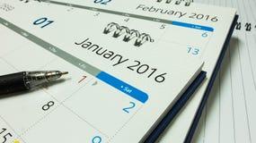 Plan für neues Jahr 2016, Kalender von 2016 mit Stift und Notizbuch auf Schreibtisch Lizenzfreie Stockbilder