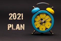 Plan 2021 geschrieben mit Wecker auf schwarzen Papierhintergrund Stockfotografie