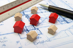 Plan of a house with a pen. Some little houses on a plan, real estate or buildings Royalty Free Stock Photos