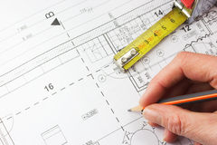 Plan of a house, ruler and a hand writing with a pencil. Plan of a house with a ruler and a hand writing with a pencil royalty free stock photos