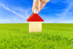 Plan of a house in safe and clean environment. Male hand putting wooden toy house on beautiful green meadow. Concept on planing to build a house in safe and Royalty Free Stock Photos
