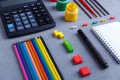 Plan ihrer Bleistifte und Zeichenstifte, des Taschenrechners, des Notizbuches und der hellen Farben mit Bürsten Stockbild