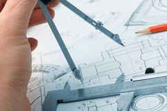 The plan industrial details. And a hand with divider. A photo closeup. Blue toning royalty free stock photo