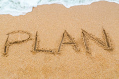 PLAN inscription written on sandy beach with wave approaching Stock Photography