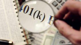Plan 401k wird mit Vergrößerungsglas aufgepasst stock footage