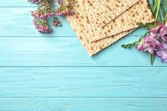 Plan lekmanna- sammansättning av matzoen och blommor på träbakgrund Påskhögtid Pesach Seder royaltyfri bild