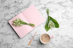 Plan lekmanna- sammans?ttning med anteckningsboken, liljekonvaljbuketter och kaffe p? marmorbakgrund arkivbilder