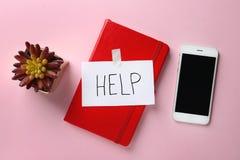Plan lekmanna- sammansättning med anteckningsboken, ordet HJÄLP och smartphonen på färgbakgrund arkivbild