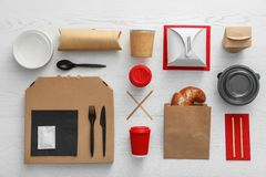 Plan lekmanna- sammansättning med den pappers- påsen och olika takeaway objekt på träbakgrund royaltyfri bild