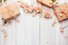 Plan lekmanna- sammansättning med gåvaaskar som slås in i den kraft papper och rosen royaltyfri bild