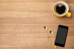 Plan lekmanna- sammansättning med hörlurar, smartphonen, koppen kaffe och utrymme för text arkivfoto