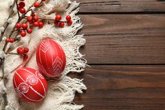 Plan lekmanna- sammansättning med målade röda påskägg på trätabellen royaltyfri foto