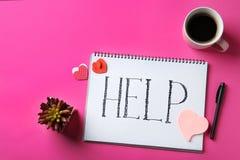 Plan lekmanna- sammansättning med pappers- hjärtor, koppen kaffe, anteckningsboken och ordet HJÄLP royaltyfria foton