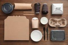 Plan lekmanna- sammansättning med pappers- påsar och olika takeaway objekt på träbakgrund arkivbild