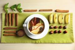 Plan lekmanna- sammansättning med smakligt kanelbrunt te på tabellen royaltyfri bild