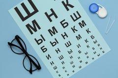 Plan lekmanna- sammans?ttning med kontaktlinser, exponeringsglas och tillbeh?r p? bl? bakgrund royaltyfria foton