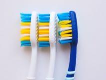 Plan lekmanna- sammans?ttning med manuella tandborstar p? vit bakgrund Tandborste och toothpaste den op sikten, l?genhet l?gger M arkivbilder