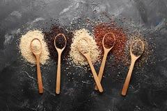 Plan lekmanna- sammans?ttning med olika typer av quinoaen p? svart bakgrund royaltyfri bild