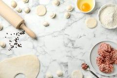 Plan lekmanna- sammans?ttning med r? klimpar och ingredienser p? marmorbakgrund Process av matlagning royaltyfria foton