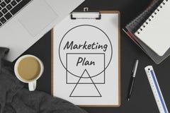 Plan marketing écrit sur le livre blanc placé avec l'ordinateur portable Images stock