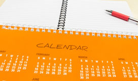 Plan for New Year, Orange Calendar with Pen and Notebook on Office Desk Stock Images