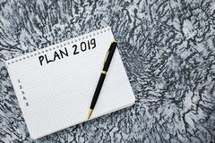 Plan for 2019, notepad and pen on a textured gray background stock image