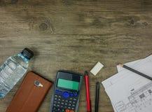 Plan, papeterie et calculatrice de bâtiment de vue supérieure sur le fond en bois gris Photographie stock libre de droits