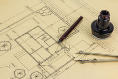 Plan, pen, ink and compass. Old fashioned drawing tools lying on an architects hand drawn plan Royalty Free Stock Image