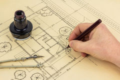 Plan, pen, ink, compass and hand. Architect draws a plan in an old fashioned way Stock Photos