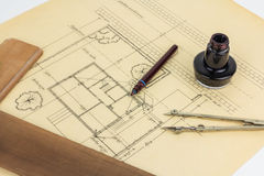 Plan, pen, ink, compass and ruler. Old fashioned drawing tools placed on an architectual plan drawing Royalty Free Stock Photo