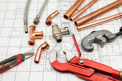 Plan plumber. Plumbing Tools Arranged On House Plans whit copper tubes Stock Image