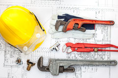 Plan plumber. Plumbing Tools Arranged On House Plans whit wrench Royalty Free Stock Image