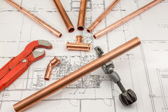 Plan plumber. Plumbing Tools Arranged On House Plans whit wrench and pipe cutter Royalty Free Stock Photography