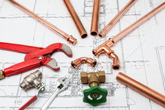 Plan plumber. Plumbing Tools Arranged On House Plans whit wrench and pipe cutter Stock Photography