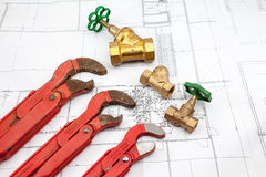 Plan plumber. Plumbing Tools Arranged On House Plans whit wrench and water valves Royalty Free Stock Photography