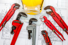 Plan plumber. Plumbing Tools Arranged On House Plans whit wrench and water valves Stock Photos