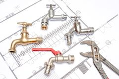 Plan plumber and wrench. Plumbing Tools Arranged On House Plans whit wrench and water valves Stock Photo